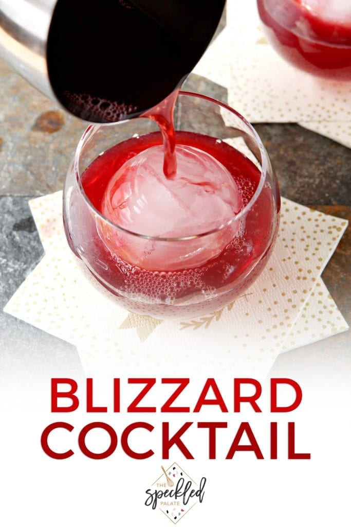 A silver cocktail shaker pours red liquid into an old fashioned glass with a large spherical ice cube with the text 'blizzard cocktail'