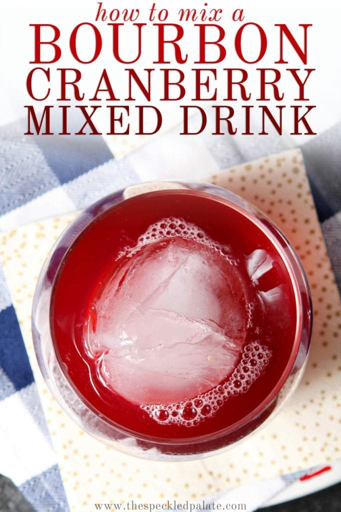 Close up of an old fashioned glass holding red liquid with the text 'how to mix a bourbon cranberry mixed drink'