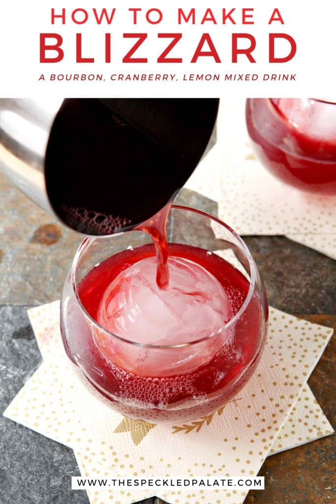 A silver cocktail shaker pours red liquid into an old fashioned glass with a large spherical ice cube with the text 'how to make a blizzard. a bourbon, cranberry, lemon mixed drink.'