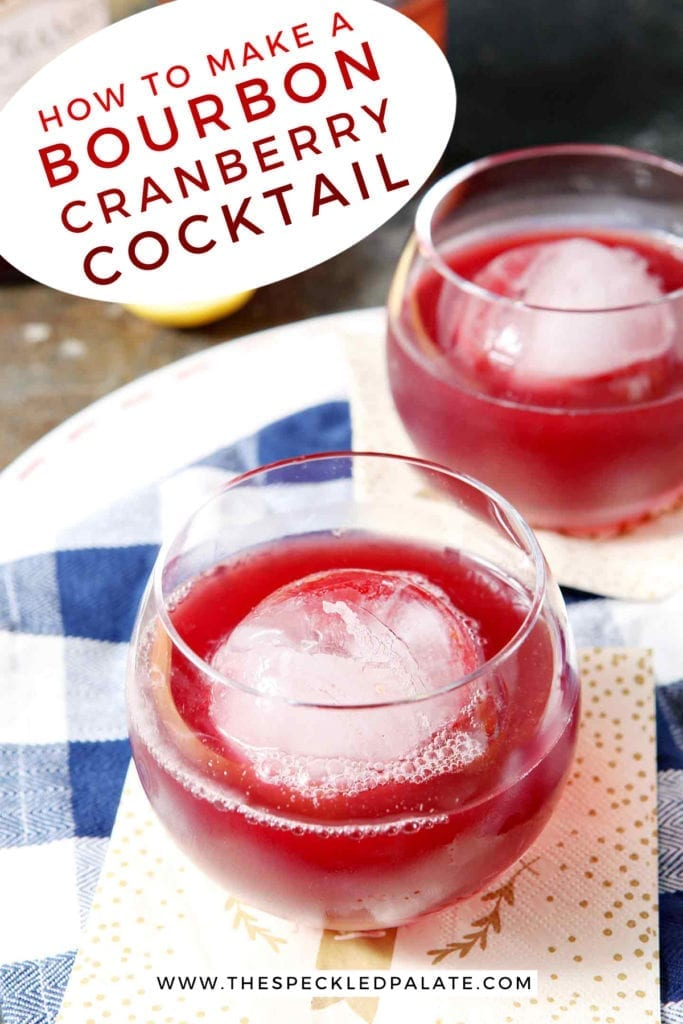 Two red drinks in old fashioned glasses with large spherical ice cubes sit on a blue and white buffalo check napkin with the text 'how to make a bourbon cranberry cocktail'
