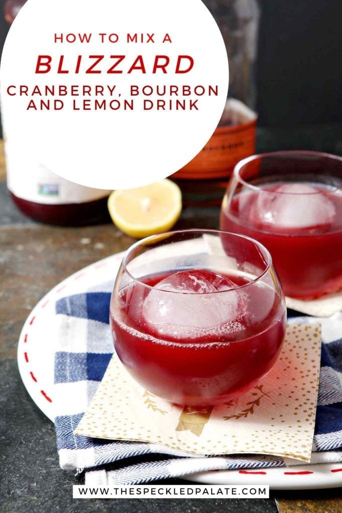 Two red drinks in old fashioned glasses with large spherical ice cubes sit on a blue and white buffalo check napkin with the text 'how to mix a blizzard: cranberry, bourbon and lemon drink'