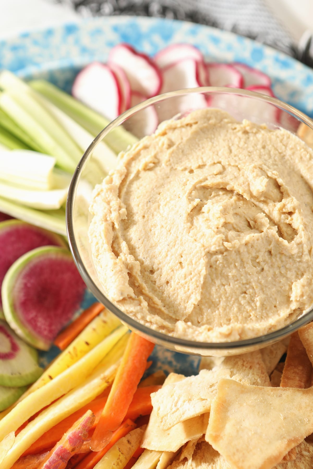 Close up of hummus dip in a clear glass bowl surrounded by veggie slices