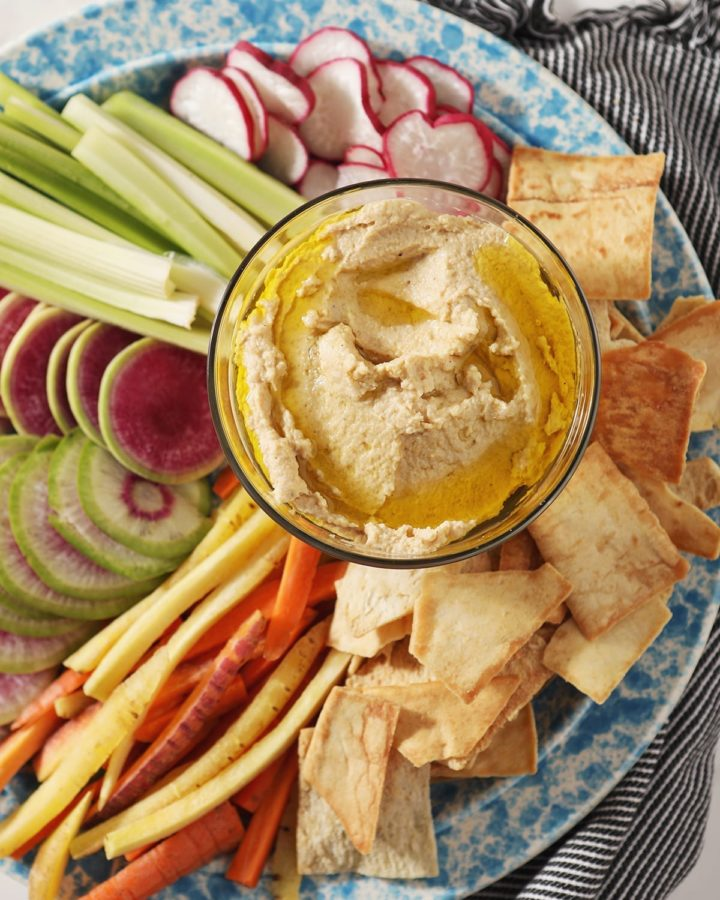 Hummus, drizzled with olive oil, sits in a glass container surrounded by radish, celery and carrot slices and pita chips