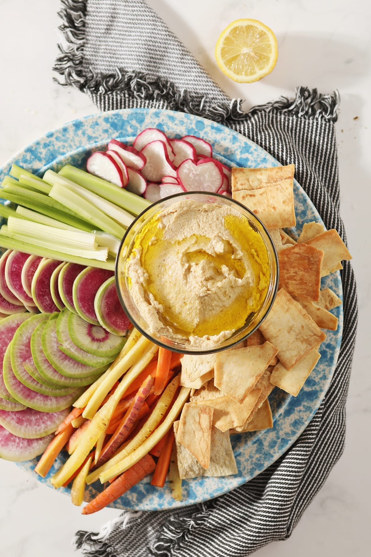 Garlic Hummus, drizzled with olive oil, sits in a glass container surrounded by radish, celery and carrot slices and pita chips