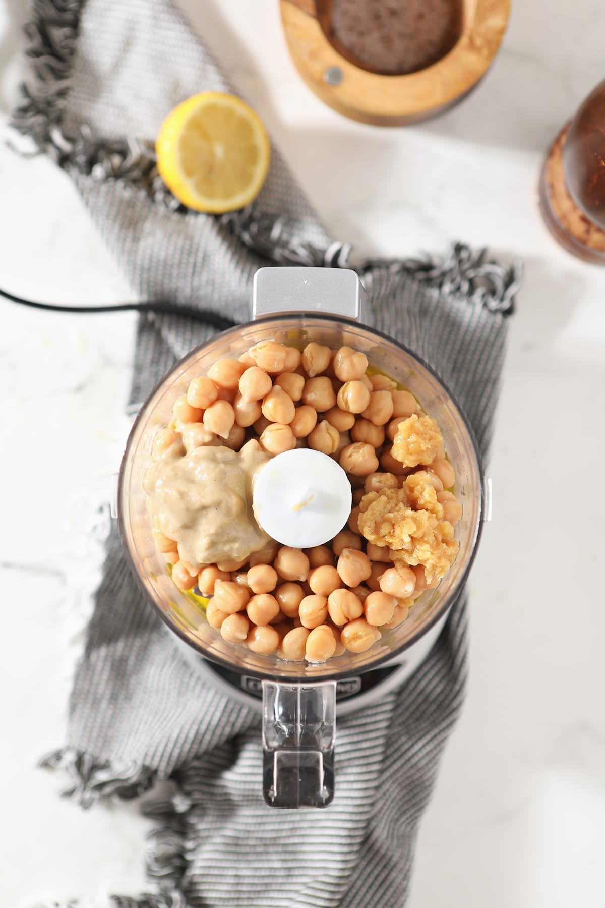 Tahini and garlic sit on top of whole chickpeas in a food processor on a striped towel on marble