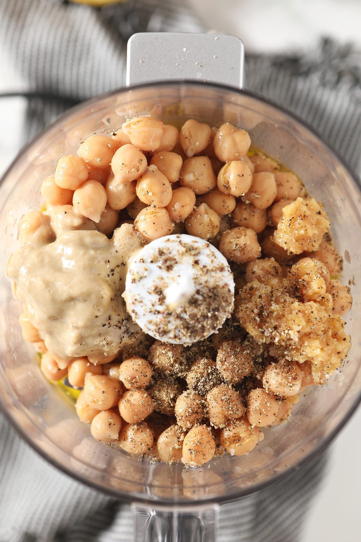 Close up of chickpeas, salt, pepper, tahini, garlic and other ingredients in a food processor before blending