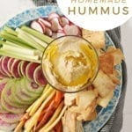 """Hummus, drizzled with olive oil, sits in a glass container surrounded by radish, celery and carrot slices and pita chips with text """"Easy 5-ingredient homemade hummus"""""""