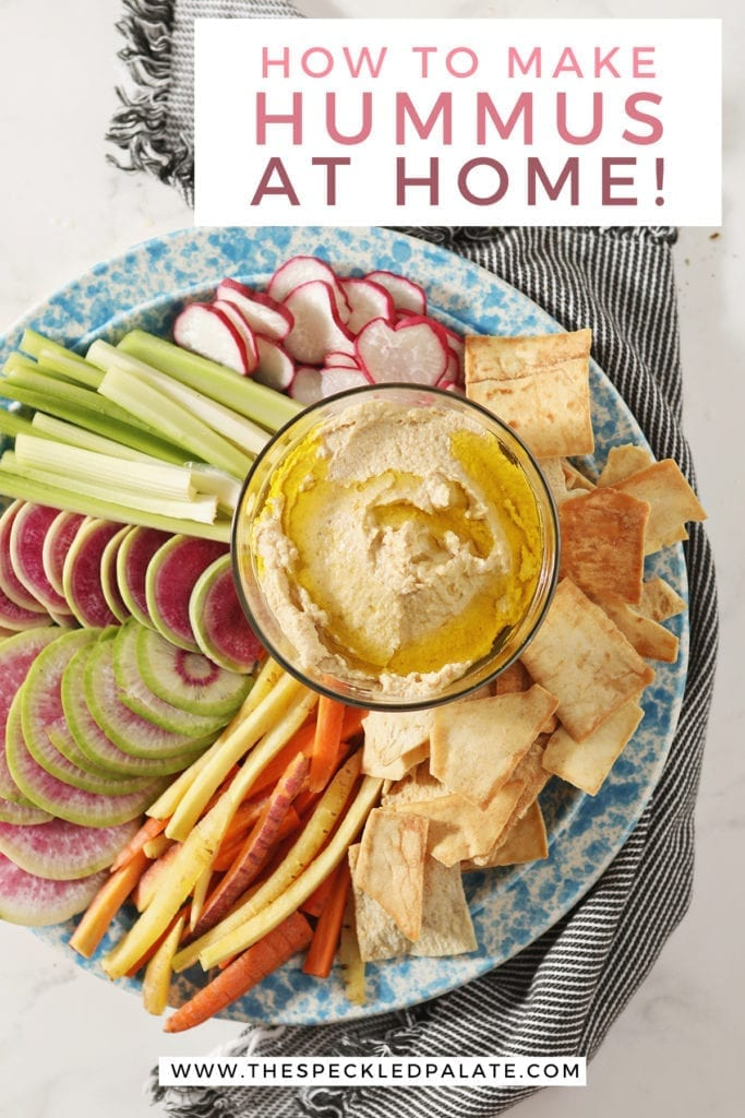 """Hummus, drizzled with olive oil, sits in a glass container surrounded by radish, celery and carrot slices and pita chips with text """"How to Make Hummus at Home!"""""""