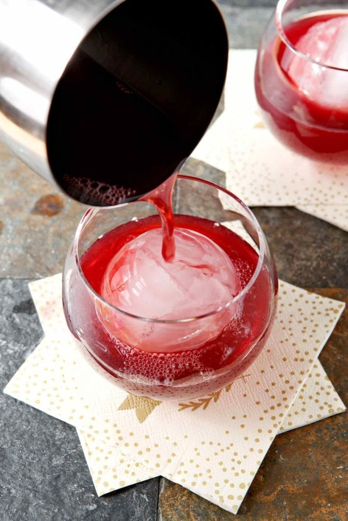 A cranberry cocktail is poured into a rocks glass with a giant spherical ice cube