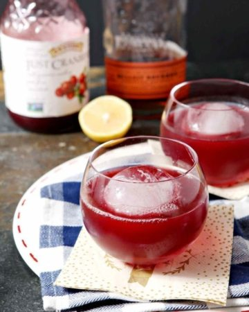 Two Blizzard Bourbon Cranberry Cocktails sit on a platter, ready for drinking