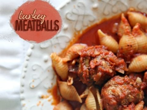 Close up of two Turkey Meatballs in sauce with shell pasta on a white plate from above