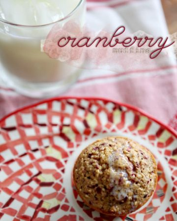 A Fresh Cranberry Muffins with melted butter on top sits on a patterned red plate next to a glass of milk