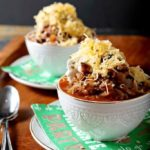 Two bowls of Hearty Shiner Bock Chili are served on a wooden platter