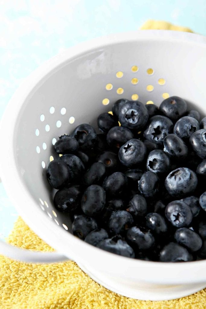 Fresh blueberries, in a white colander, on a yellow towel