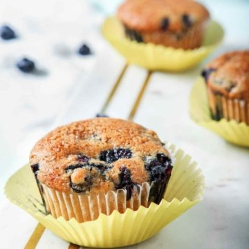 Vegan Blueberry Muffins, on a marble serving board, are ready for eating.