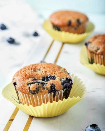Vegan Blueberry Muffins, on a marble serving board, are displayed and ready to eat