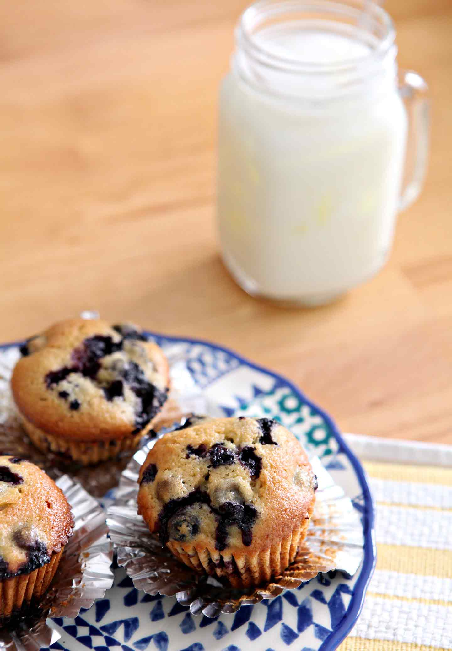 Three Vegan Blueberry Muffins, set on a blue patterned plate on a golden tabletop with a glass of nut milk before eating.