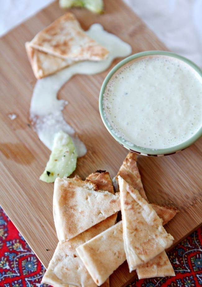 A green bowl of homemade Tzatziki Sauce sits on a wooden cutting board with slices of pita bread and cucumber rounds