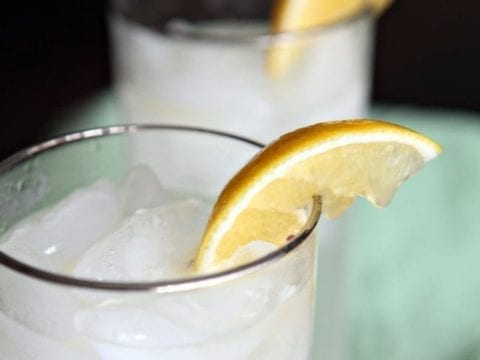 Two silver-lined glasses with Tom Collins are garnished with lemon wedges