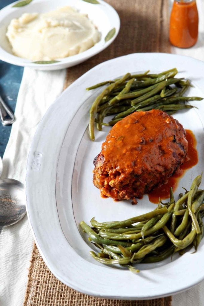 A whole Slow Cooker Turkey Meatloaf sits alongside green beans (with mashed potatoes in the background) before serving.