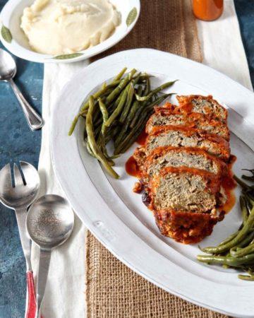 Sliced Slow Cooker Turkey Meatloaf is served on a white platter alongside green beans.
