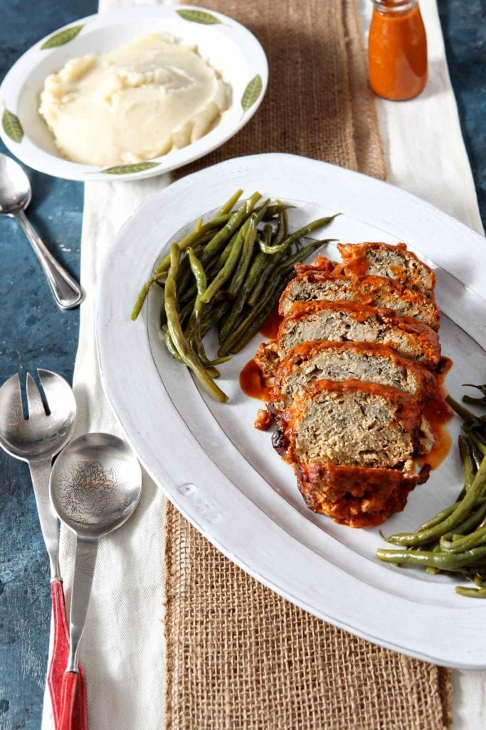 Sliced Slow Cooker Turkey Meatloaf is served on a white platter alongside green beans.