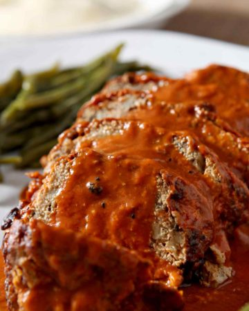 Close up of sliced Slow Cooker Turkey Meatloaf, smothered in tomato sauce, before serving