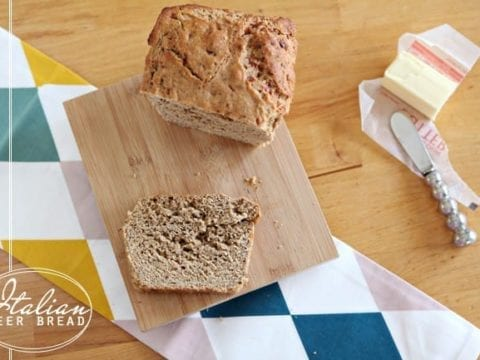 A slice of Whole Wheat Italian Beer Bread on a wooden cutting board with the rest of the loaf sit on a wooden tabletop next to a stick of butter and a butter knife