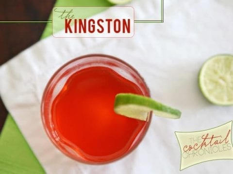 A glass of bright red liquid garnished with a lime round sits on top of a white napkin