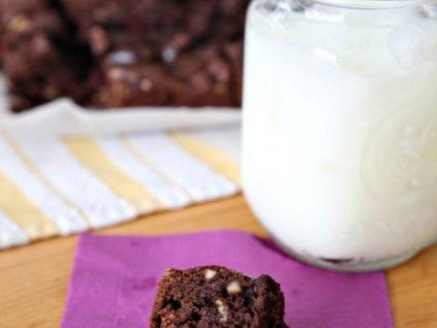 A piece of brownie sits on purple napkin next to glass jar of milk