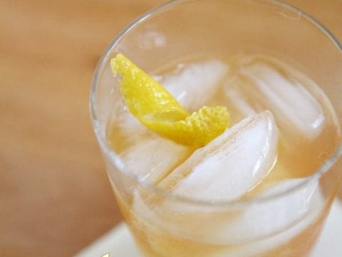 A close up of a cocktail glass holding a golden drink with a lemon twist