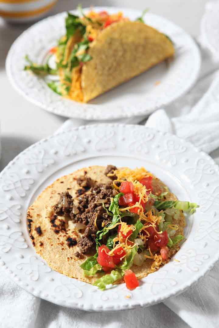 A soft tortilla holds ground beef and other taco toppings, before consuming