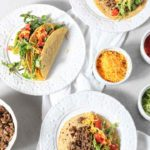 Overhead image of several Ground Beef Tacos on plates