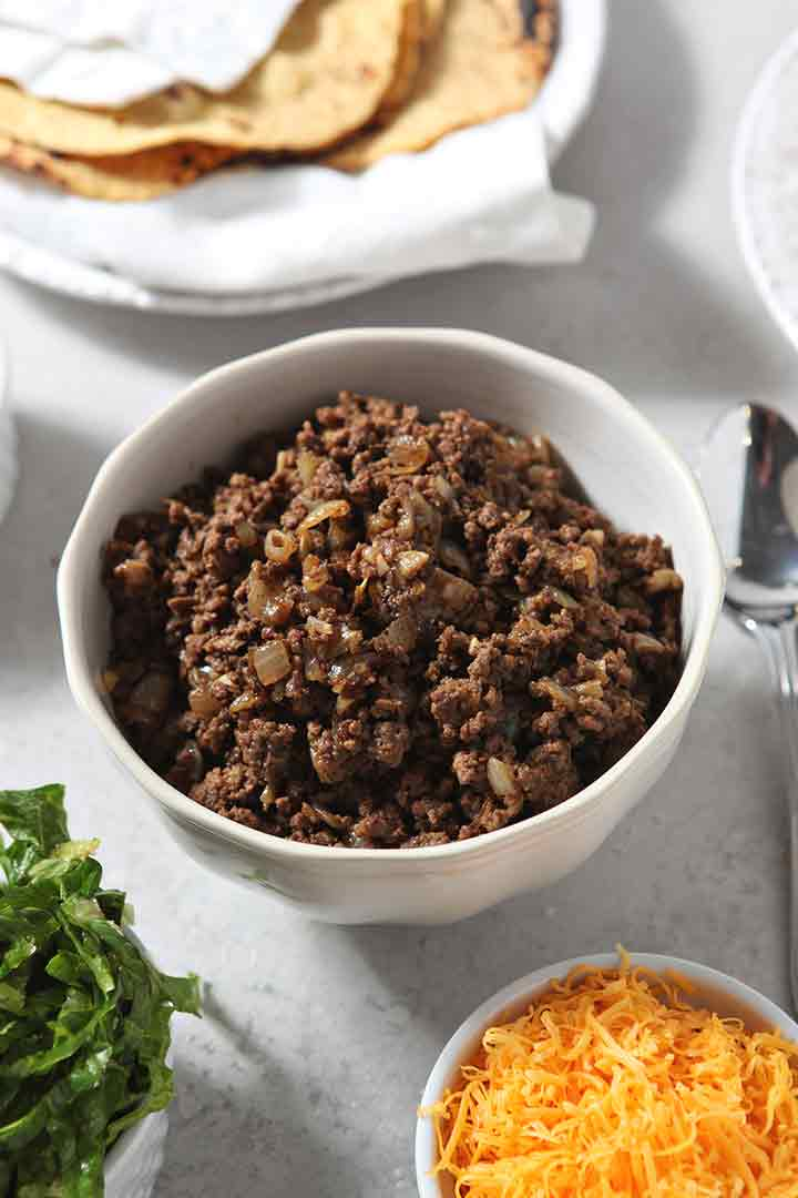 Cooked ground beef and onions are served with taco toppings for guests