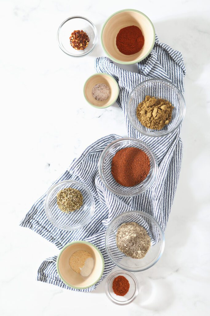 Spices for a homemade spice blend on a blue towel