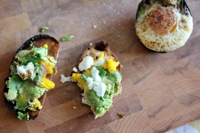 Two pieces of avocado toast with egg on a wooden cutting board