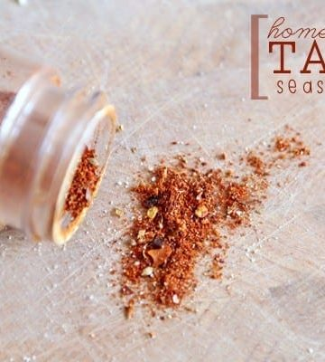 Taco Seasoning sprinkles out of a plastic jar holding it onto a wooden cutting board