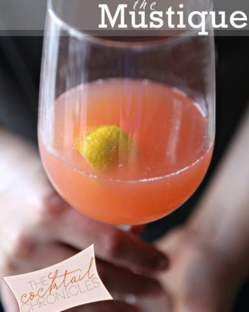 A woman holds a wine glass of a pink liquid with a lemon peel in it