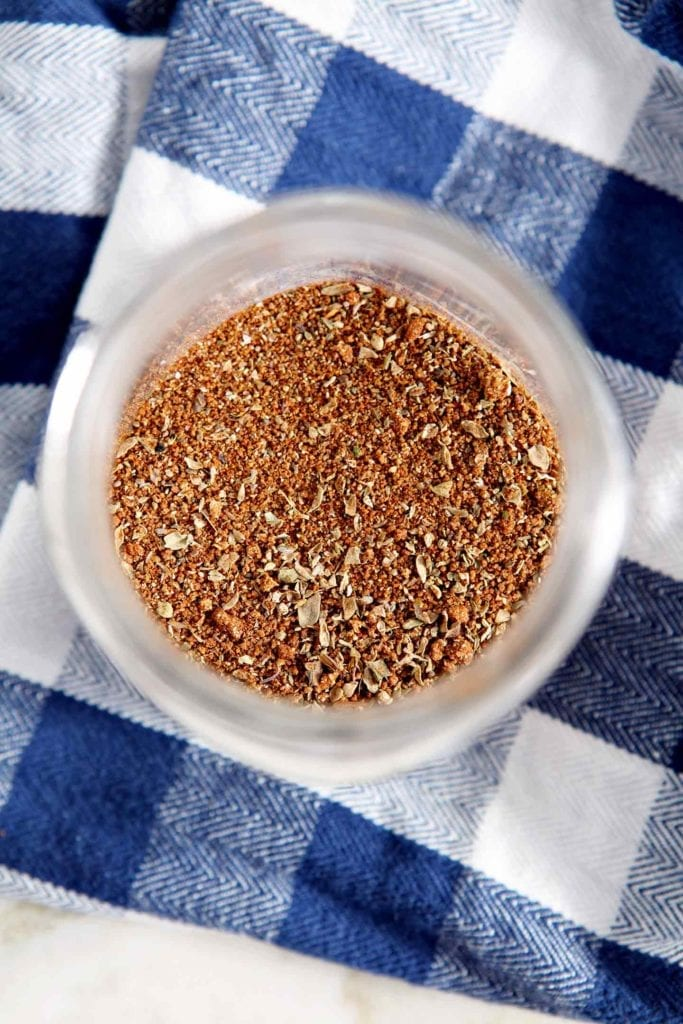Overhead of a BBQ dry rub blend inside a glass jar on top of a blue and white checked napkin