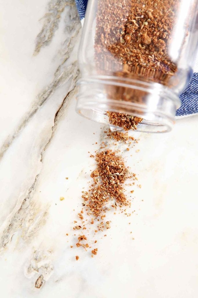 Overhead of an overturned glass jar holding a spice blend and the spice spilling out onto a marble counter