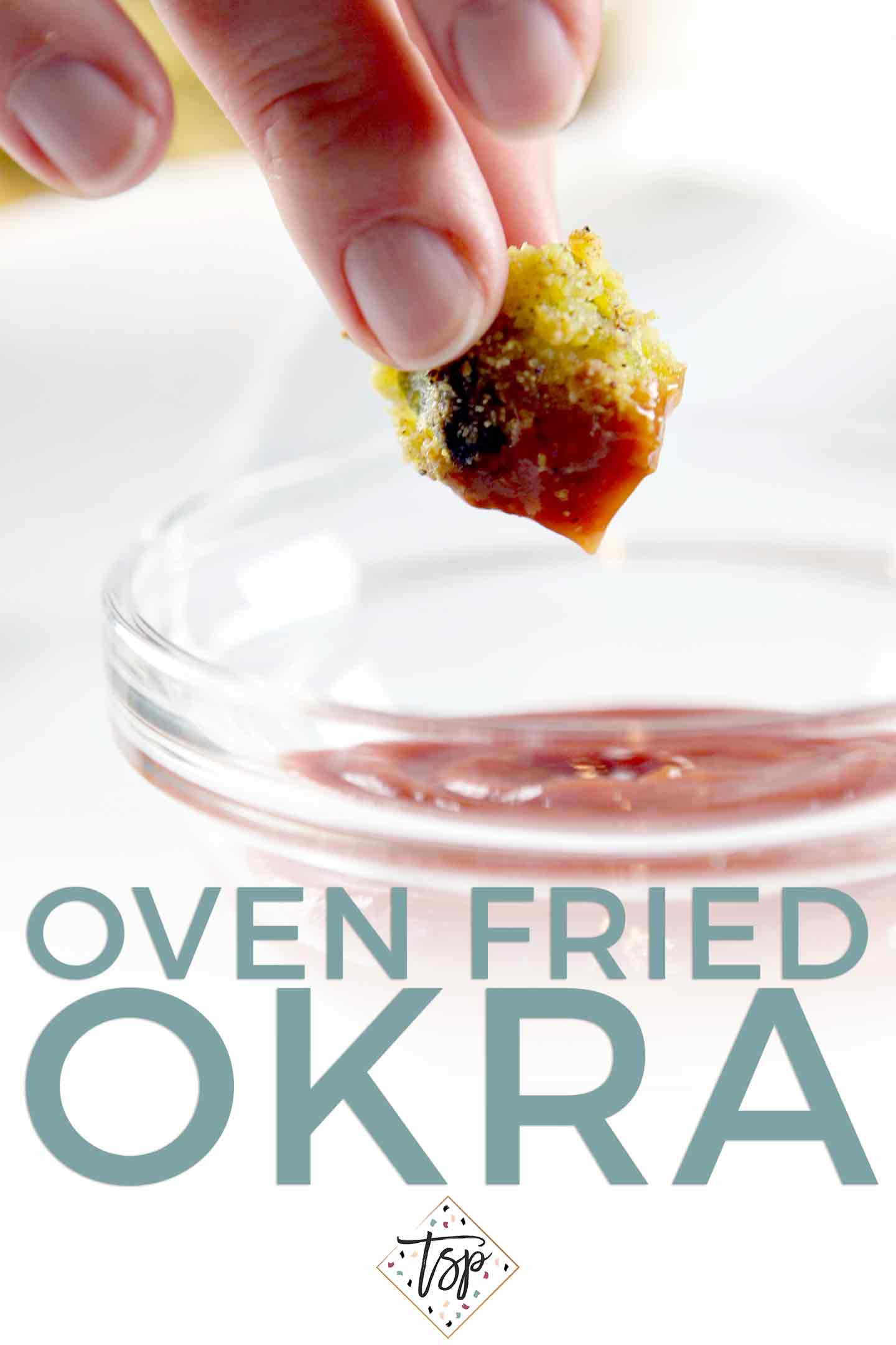 A woman dips a piece of Oven Fried Okra in a small glass bowl of ketchup before eating.