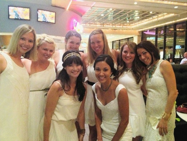 Eight women wear white dresses and smile at the camera