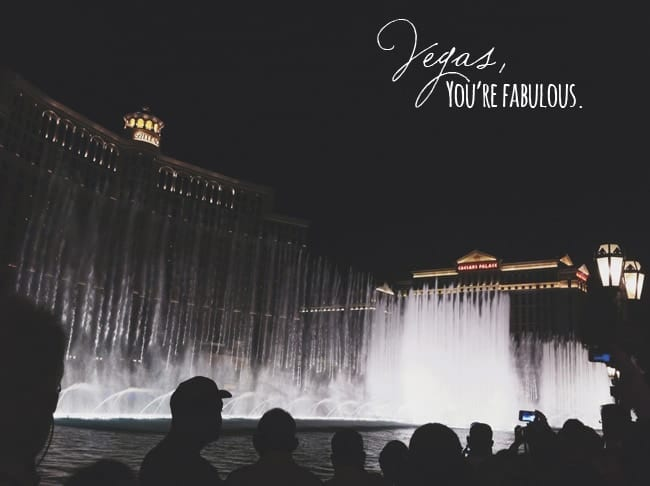 "Fountains in front of the Bellagio in Vegas at night with people silhouetted in front of it with text saying, ""Vegas, you're fabulous"""