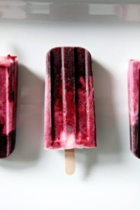 Three Blackberry and Strawberry Yogurt Popsicles on a white platter