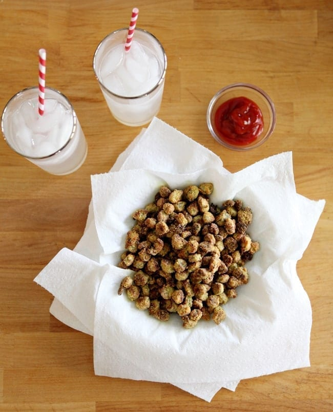Overhead of Oven Fried Okra on top of paper towels with a bowl of ketchup and two lemonades