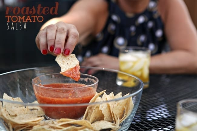 A woman with red nails dips a tortilla chip into a bowl of salsa
