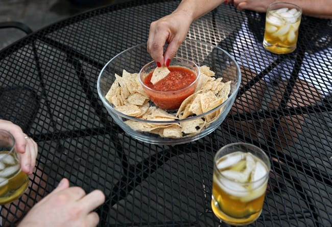 A woman with red nails dips a tortilla chip into a bowl of salsa while surrounded by three glasses of a golden liquid