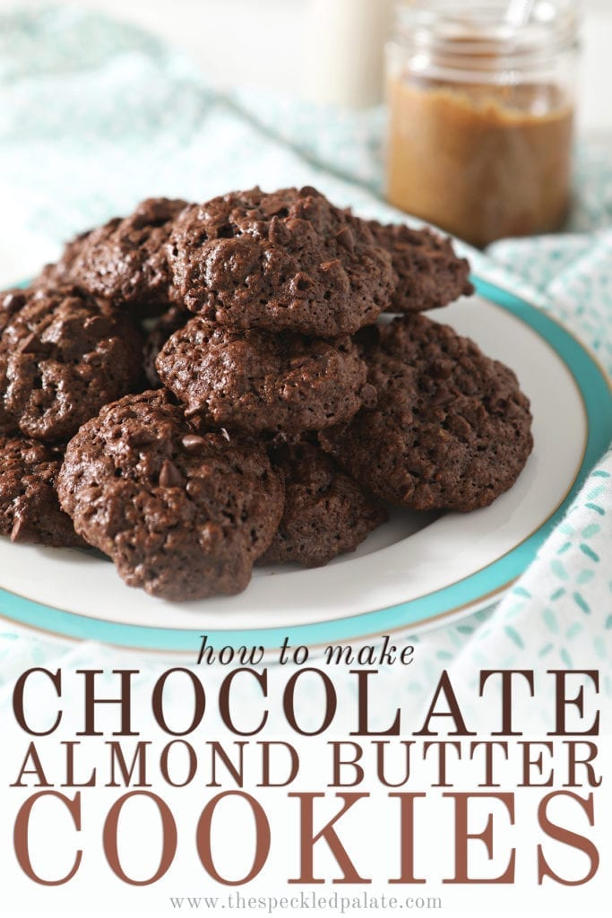 A turquoise-rimmed plate holds a stack of chocolate almond oat cookies sitting on a patterned aqua and white towel with a jar of almond butter and a glass of almond milk behind it with the text 'how to make chocolate almond butter cookies'