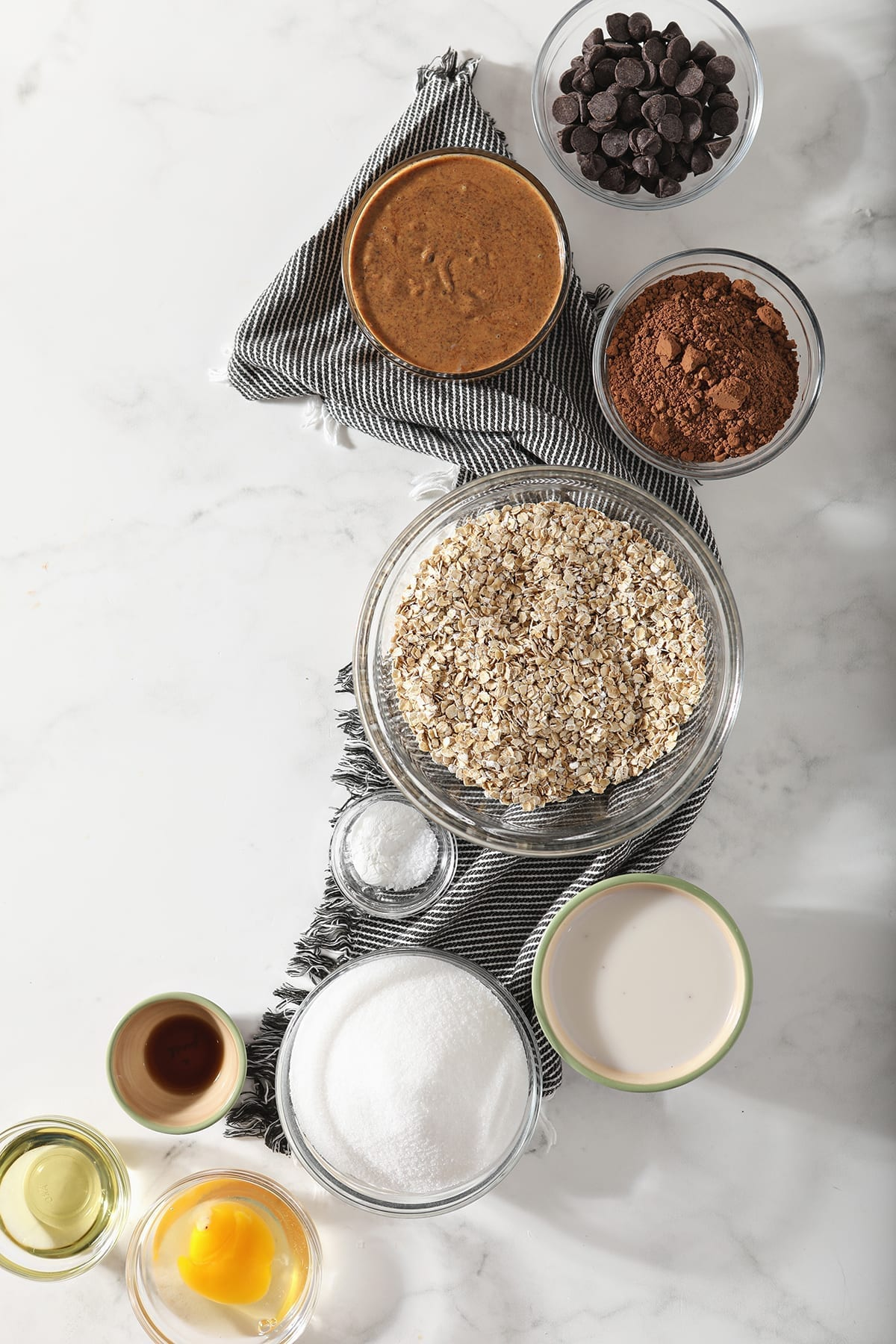Overhead image of the ingredients for gluten free cookies on a gray and white striped towel
