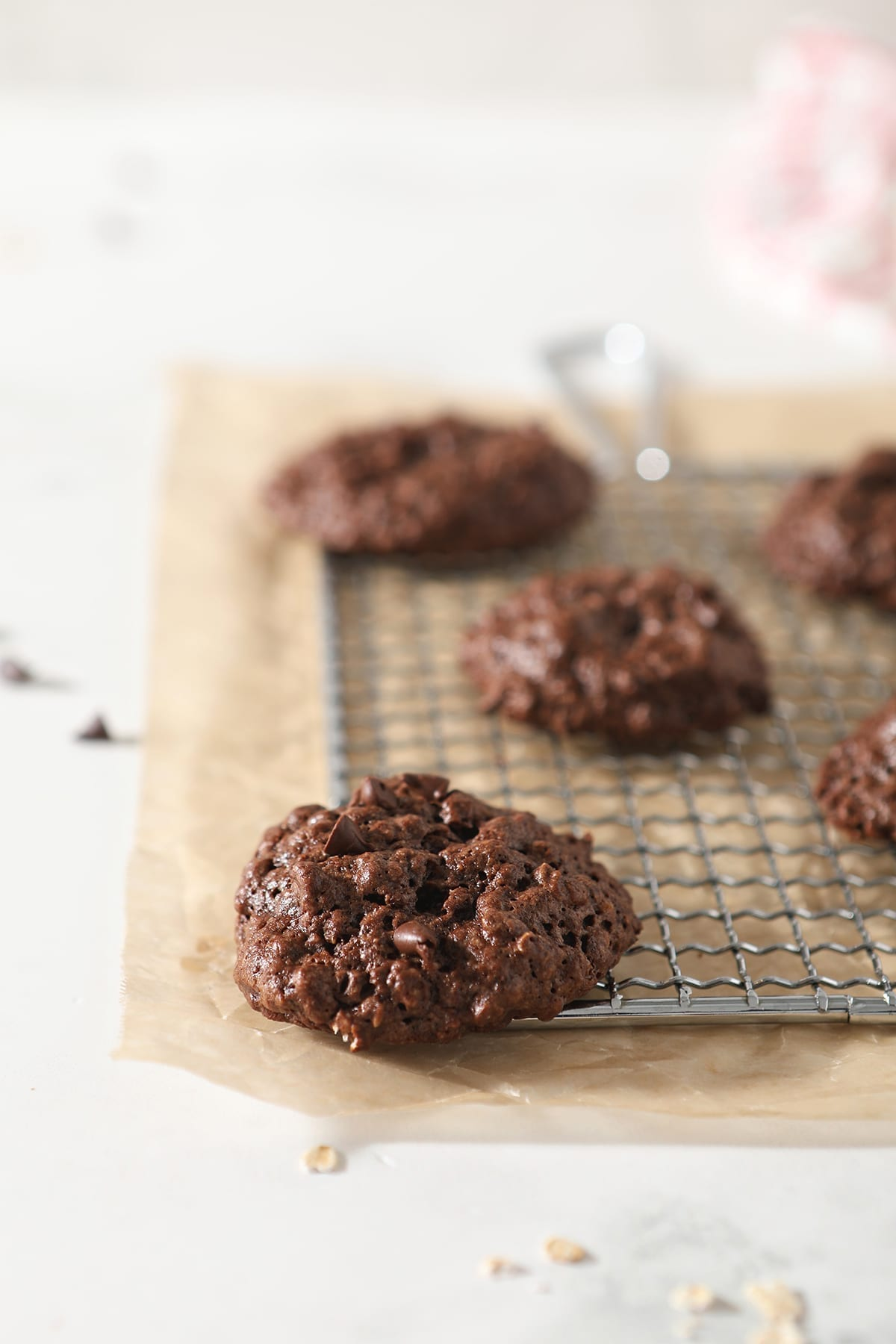 A few Gluten Free Chocolate Cookies sit on a metal grate on top of parchment paper